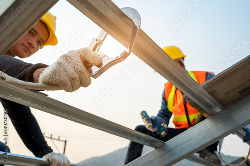 Obraz Construction worker wearing safety harness belt during working at high place and installing concrete roof tile on top of the new roof,Concept of residential building under construction. - fototapety do salonu