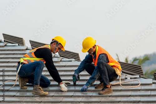 Obraz Construction worker wearing safety harness belt during working on roof structure of building on construction site,Roofer using air or pneumatic nail gun and installing concrete roof tile on top roof. - fototapety do salonu