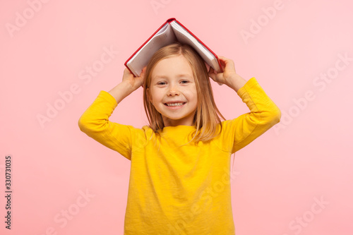 Fototapeta Portrait of happy lazy little girl covering head with book and smiling to camera, disobedient child having fun, fooling around instead studying lesson. indoor studio shot isolated on pink background obraz