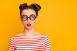 Closeup photo of pretty lady student send air kiss strange facial expression look side empty space wear circle freak specs striped red white shirt isolated bright yellow color background
