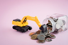 The Excavator Loader Model With Pile Of Coins In The Glass Jar On Pink Background For Saving Money, Investment, Business And Finance Concept