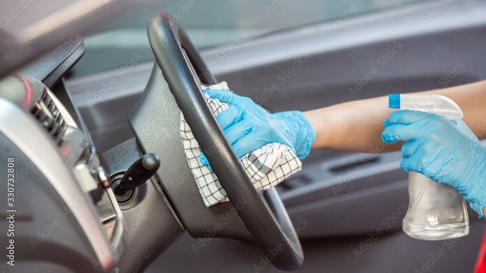 Fototapeta Cleansing car interior and spraying with disinfection liquid. Hands in rubber protective glove disinfecting vihicle inside for protection from virus corona disease