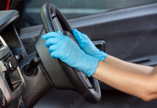 Obraz Hands in rubber protective gloves driving vihicle for protection from virus corona disease - fototapety do salonu