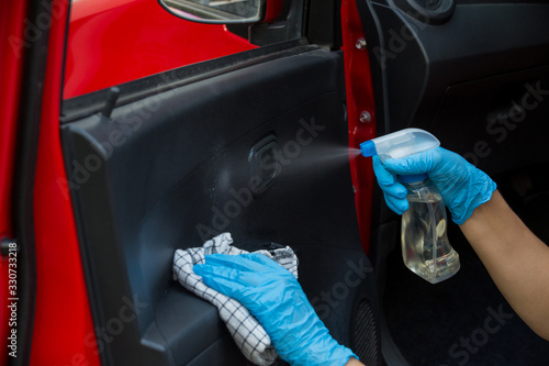 Obraz Cleansing car interior and spraying with disinfection liquid. Hands in rubber protective glove disinfecting vihicle inside for protection from virus corona disease - fototapety do salonu