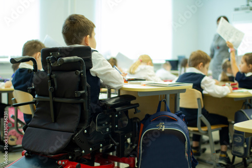 Obraz A disabled student in a wheelchair in primary school. - fototapety do salonu