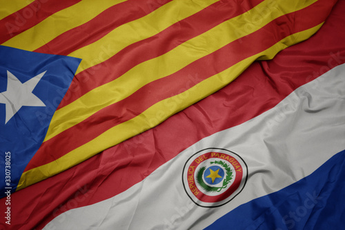 Photo waving colorful flag of paraguay and national flag of catalonia.