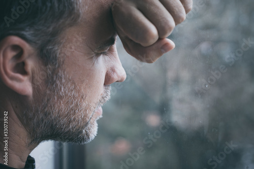 Photo portrait one sad man standing near a window