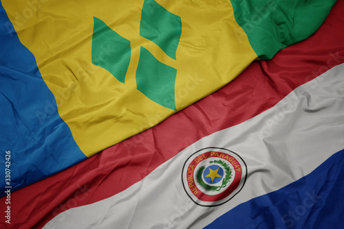 waving colorful flag of paraguay and national flag of saint vincent and the grenadines Canvas Print