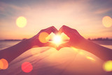 Female hands heart shape on nature bokeh sun light flare wave and blur tropical beach abstract background.