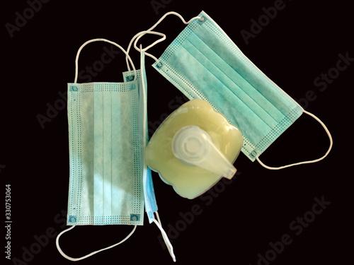Photo Tres mascarillas de papel para la protección contra los virus y dispensador de jabón para la higiene de manos