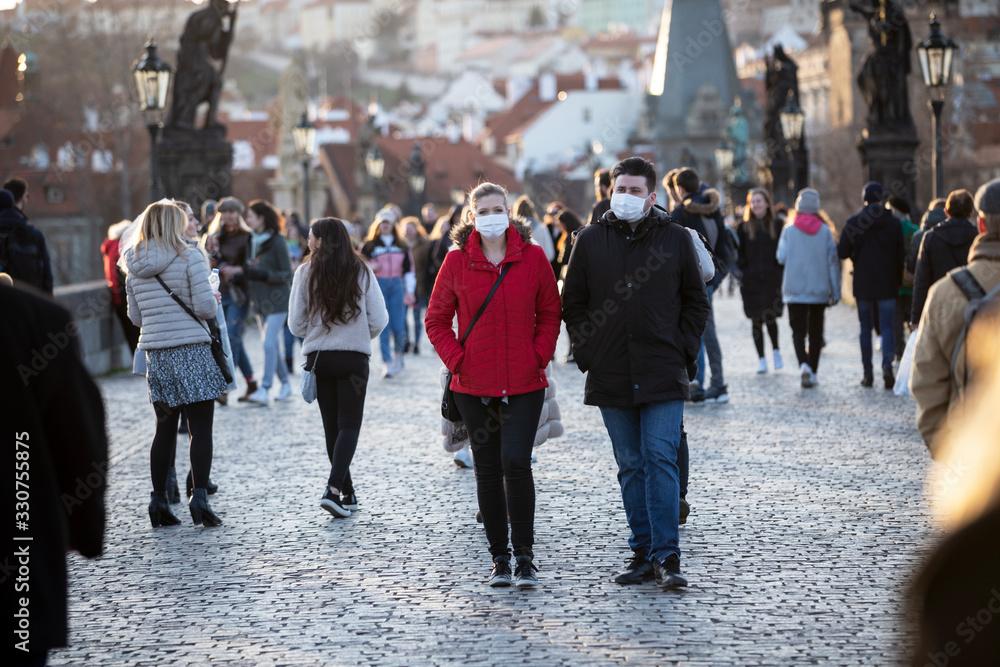 Fototapeta Couple walking with the veils the historical centrum in Prague, Czech Republic, Europe during pandemic of coronavirus.