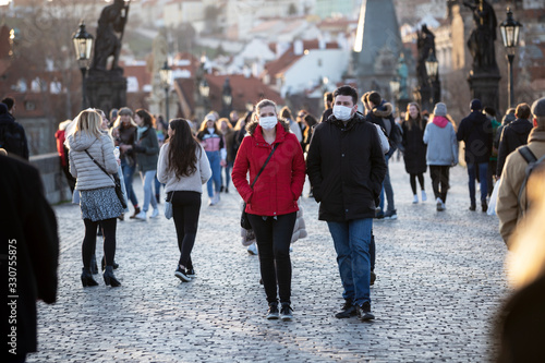 Obraz Couple walking with the veils the historical centrum in Prague, Czech Republic, Europe during pandemic of coronavirus. - fototapety do salonu