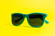 canvas print picture - Close-up of cyan sunglasses, on background of yellow color.