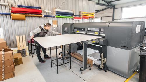 Fototapeta Technician operator works on large premium industrial printer plotter machine obraz