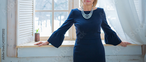 Fototapeta Portrait of a stunning elegant mature woman in a blue tight-fitting dress standing by the window, Art Nouveau style