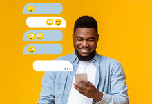 Millenial African American Guy Using Smartphone For Chat Communication On Orange Background, Empty Space