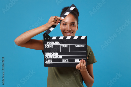 Fényképezés Smiling young african american woman girl in casual t-shirt posing isolated on bright blue background