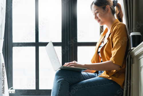 Fototapeta smart attractive asian female creative  woman happiness working with laptop casual dress sit next to window with light glow freelance work from home ideas concept obraz