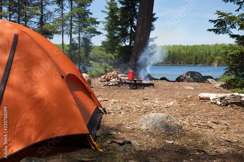 Fototapeta Campsite with orange tent and campfire on a northern Minnesota lake obraz