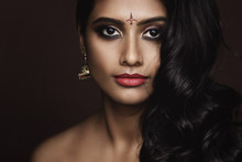 Portrait Of Indian Woman With Beautiful Makeup And Hairstyle On Brown Background
