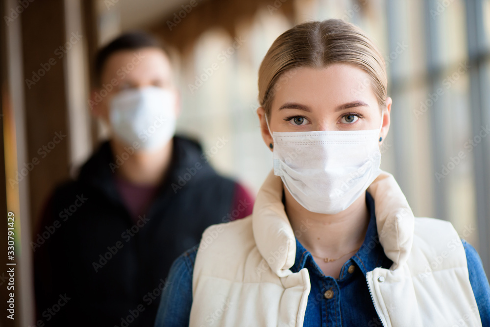 Fototapeta Man and woman wearing protective mask against transmissible infectious diseases and as protection against the flu. New coronavirus 2019-nCoV from China