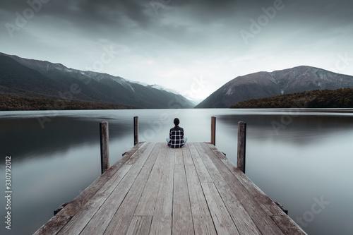Leinwand Poster A woman looking at the horizon on the rototiti lake bridge in the Tasman region,