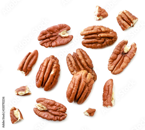 Fototapeta Peeled pecans with broken halves and pieces on a white background. The view from top. obraz