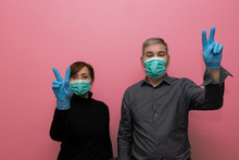 Elderly Couple Posing With Masks, And Making The Victory Sign With Their Fingers Against The Covid-19