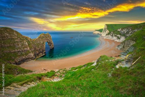 Photo Durdle Door at the beach on the Jurassic Coast of Dorset at sunset, UK