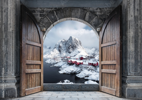 Fototapeta Large wooden door open with fishing village and rocky mountains on coastline in