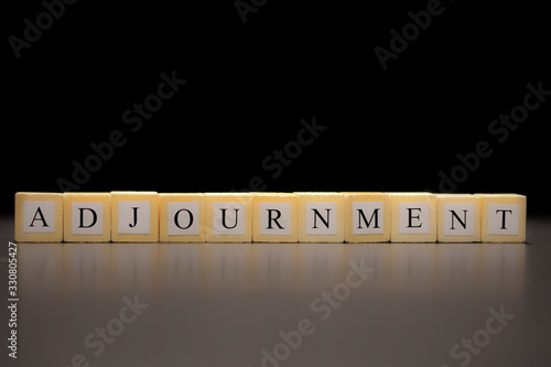 фотография The word ADJOURNMENT written on wooden cubes, isolated on a black background