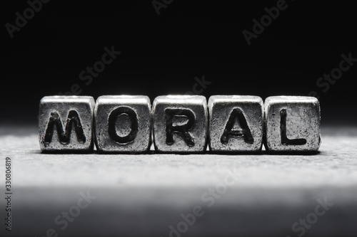 Conceptual inscription moral on metal cubes on a black gray background close-up isolated
