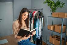 Young Woman Are Preparing A Package For Delivery To Clients. Online Clothing Store. Small Business Owner. Working Woman At Her Store. She Wearing Casual Clothing And Preparing New Orders For Today