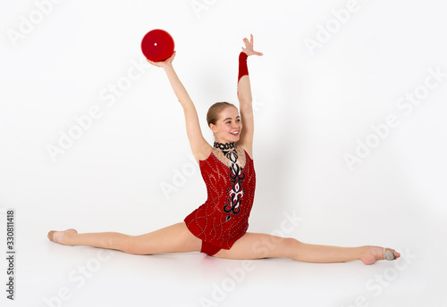 Cheerful female gymnast with ball sitting in leg split on white background