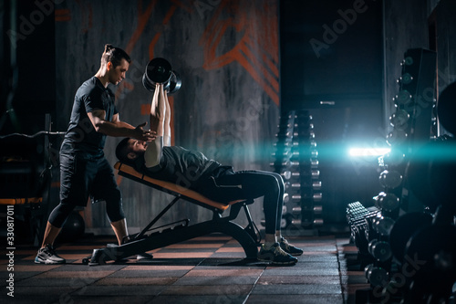 Foto young man has workout with personal trainer in modern gym