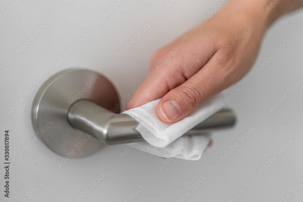 Fototapeta Coronavirus COVID-19 Prevention cleaning woman wiping doorknob with antibacterial disinfecting wipe for killing corona virus on touching surfaces or touching public bathroom handle with tissue.