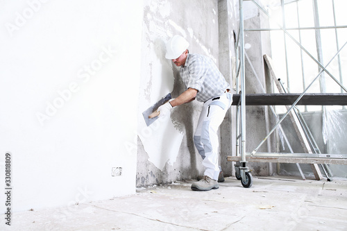 Fototapeta plasterer man at work with trowel plastering the wall of interior construction s