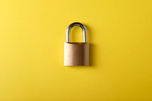 Small Metal Padlock On A Yellow Background