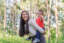 A Happy Young Mother Plays And Has Fun With Her Little Son In The Sun On A Warm Spring Or Summer Day. The Concept Of A Happy Family, Motherhood. Mother And Child Walk