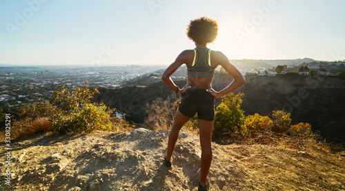 Obraz fit african american woman hiking runyon canyon stopping to see view of sunset - fototapety do salonu