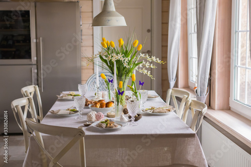 Easter festive spring table setting decoration, eggs in nest, fresh yellow tulips, marshmallows, selective focus