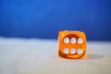 Closeup Shot Of An Orange Dice...