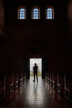 Silhouette Of A Mans Standing At The Church Entrance, Dark, Unrecognizable Interior