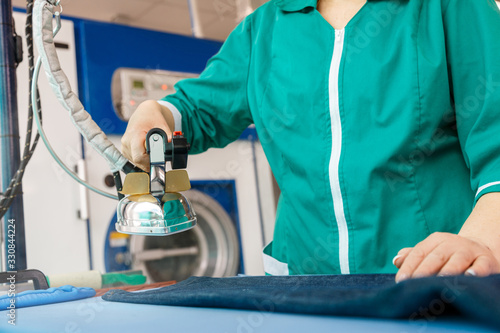 Fotografering Female hand ironing blue jeans in a dry cleaning  service