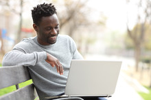 Happy Black Man Using A Laptop In A Park