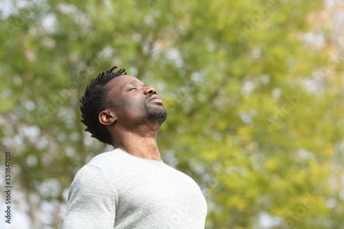 Fototapeta Black serious man breathing fresh air in a park obraz