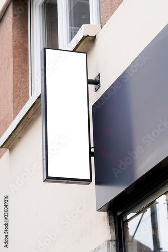 Obraz vertical white signage on shop front street - fototapety do salonu