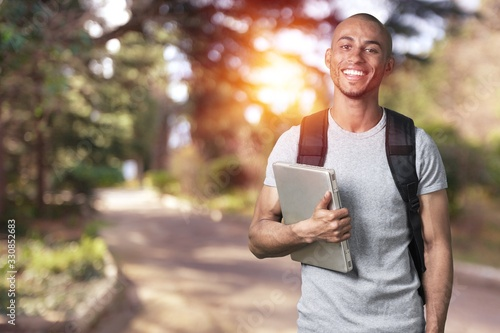 Obraz Smiling young college student with laptop - fototapety do salonu