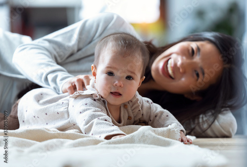 Obraz Happy young mother with his baby playing together and having fun at home. - fototapety do salonu