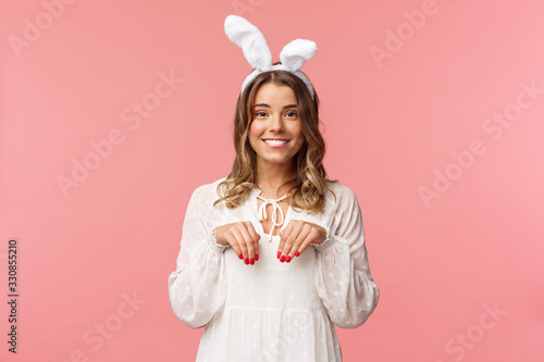 Holidays, spring and party concept. Portrait of cute and tender, lovely blond girl imitating bunny, holding hands like paws and wearing rabbit ears, smiling camera, pink background